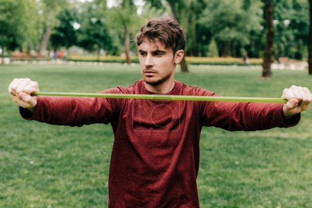 Photo for Handsome sportsman pulling up elastics band in park - Royalty Free Image