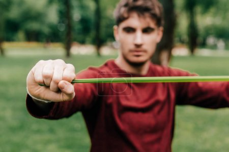 Photo for Selective focus of sportsman using elastics band while training in park - Royalty Free Image