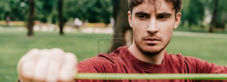 Panoramic orientation of handsome man working out with resistance band in park