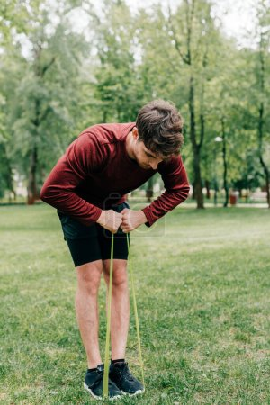 Photo for Young sportsman pulling up resistance band on lawn in park - Royalty Free Image
