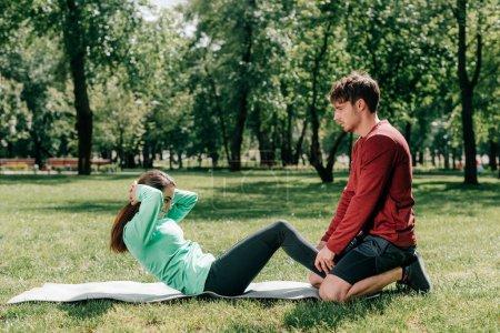 Photo pour Vue latérale de l'homme soutenant la sportive tout en s'entraînant sur un tapis de fitness dans le parc - image libre de droit