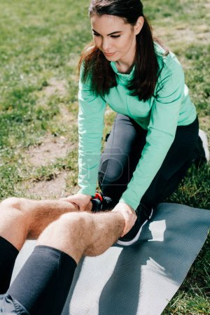 Photo for Sportswoman supporting to boyfriend during exercising on fitness mat in park - Royalty Free Image