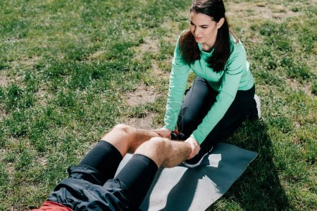 High angle view of attractive sportswoman supporting to sportsman while working out in park