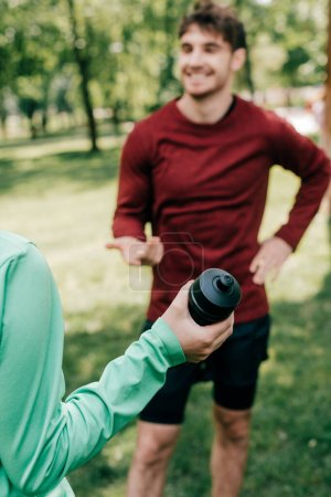 Photo for Selective focus of sportswoman holding sports bottle near smiling sportsman in park - Royalty Free Image