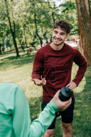 Selektiver Fokus eines gut aussehenden Sportlers im Gespräch mit Freundin mit Sportflasche im Park