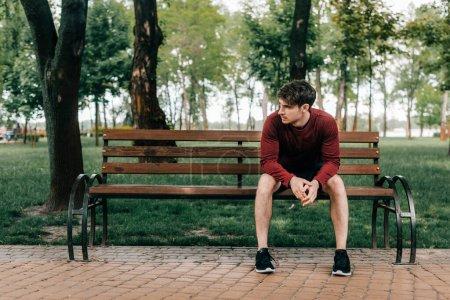Photo pour Beau sportif assis sur un banc dans le parc - image libre de droit
