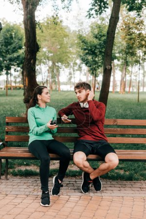 Smiling sportswoman holding sports bottle near boyfriend in headphones with smartphone on bench in park