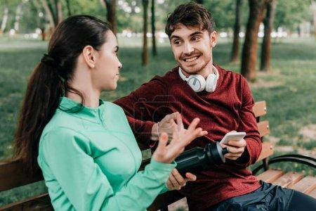 Photo pour Focus sélectif de sportif souriant dans les écouteurs tenant smartphone tout en parlant avec la petite amie sur le banc dans le parc - image libre de droit