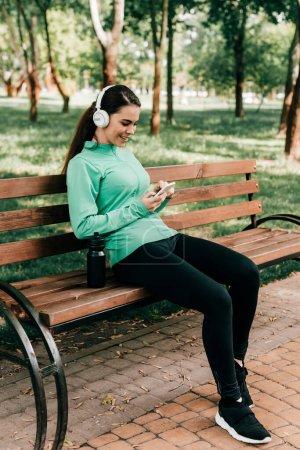 Photo pour Femme sportive souriante dans un casque en utilisant un smartphone près d'une bouteille de sport sur un banc dans le parc - image libre de droit