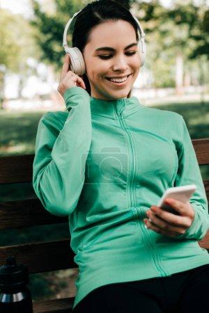Photo pour Concentration sélective d'une sportive souriante écoutant de la musique dans un casque et utilisant un smartphone sur un banc dans un parc - image libre de droit