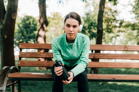 Photo for Attractive sportswoman in headphones holding sports bottle on bench in park - Royalty Free Image