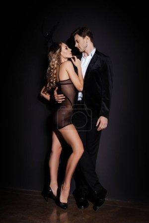 Photo pour Vue latérale d'un bel homme en costume embrassant une femme blonde sensuelle en peignoir sur fond noir - image libre de droit
