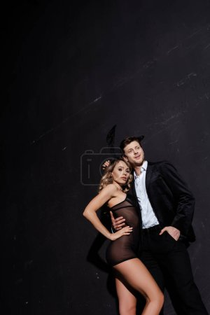 Photo pour Sensuelle fille dans les oreilles de lapin debout près de copain souriant en costume sur fond noir - image libre de droit