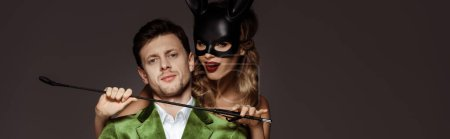 Photo for Panoramic crop of woman in bunny mask holding flogging whip near neck of man isolated on grey - Royalty Free Image