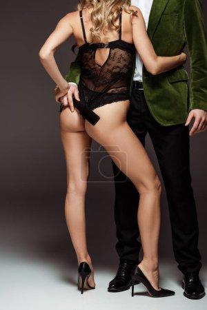 Photo pour Vue recadrée de femme sexy en body embrassant l'homme avec fessée pagaie sur fond gris - image libre de droit