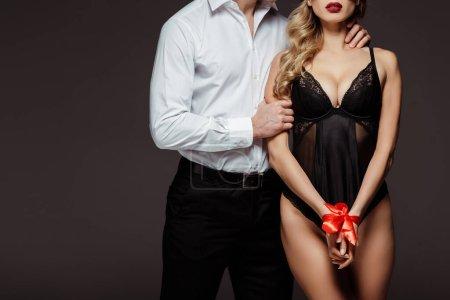 Photo pour Vue recadrée de l'homme étreignant copine sexy avec des mains attachantes avec ruban rouge isolé sur gris - image libre de droit