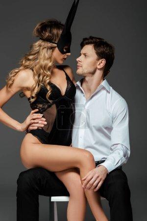 Photo pour Sensuelle femme blonde en masque de lapin assis sur petit ami isolé sur gris - image libre de droit