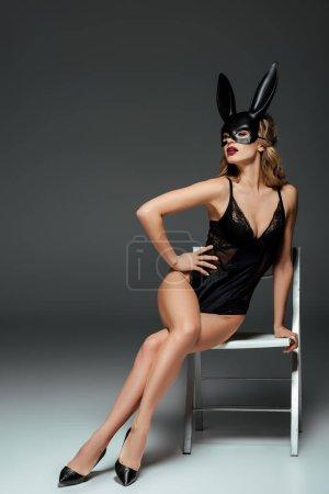 Photo pour Femme sensuelle en masque de lapin et body assis sur chaise sur fond gris - image libre de droit