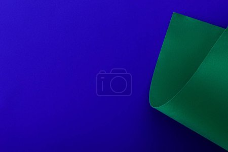 green colorful paper swirl on blue background