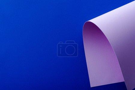 Photo pour Papier coloré violet tourbillonnant sur fond bleu - image libre de droit