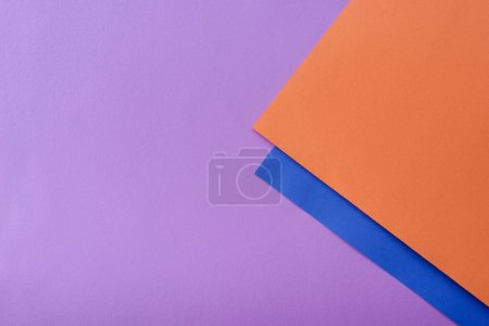 blue and orange colorful paper swirl on lilac background