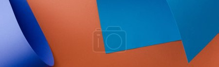 blue colorful paper on orange background, panoramic shot