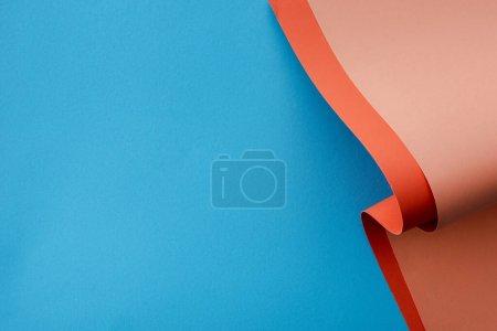 Foto de Naranja colorido papel remolino sobre fondo azul - Imagen libre de derechos