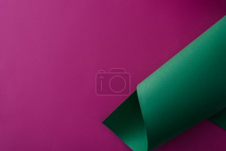 green colorful paper swirl on purple background