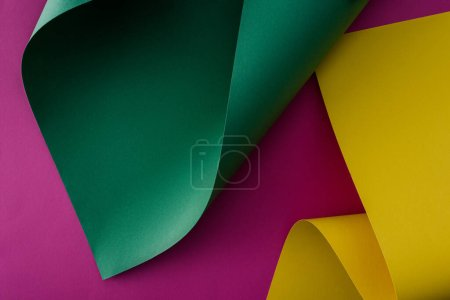 green and yellow colorful paper swirls on purple background