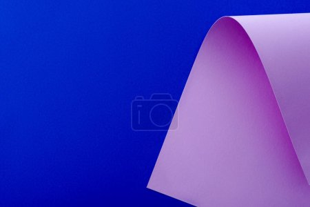 curved lilac paper on blue background