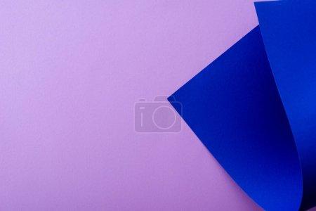 Photo pour Papier bleu courbé sur fond violet - image libre de droit