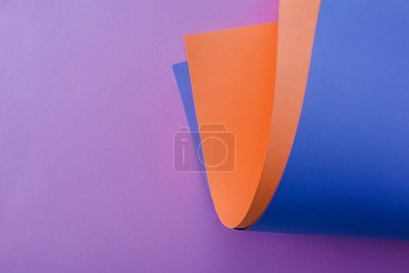 orange and blue paper on violet background