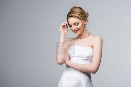 Photo pour Mariée timide en robe de mariée blanche souriant tout en touchant les cheveux isolés sur gris - image libre de droit