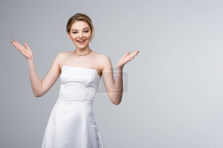 cheerful bride in white wedding dress gesturing isolated on grey