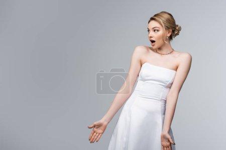 Photo pour Mariée choquée en robe de mariée blanche gesticulant et regardant loin isolé sur gris - image libre de droit