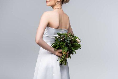 Photo pour Vue recadrée de la jeune mariée en robe de mariée blanche tenant bouquet de fleurs isolées sur gris - image libre de droit
