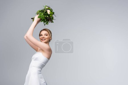Photo for Young and cheerful bride in white wedding dress holding bouquet of flowers above head isolated on grey - Royalty Free Image