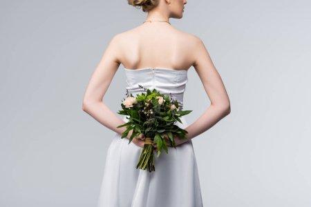 Photo pour Vue recadrée de la mariée dans une élégante robe de mariée tenant bouquet de fleurs derrière le dos isolé sur gris - image libre de droit