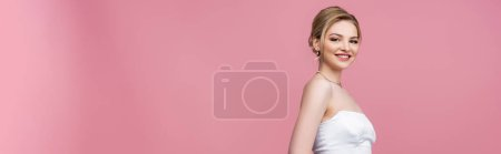 horizontal crop of bride in white wedding dress smiling on pink