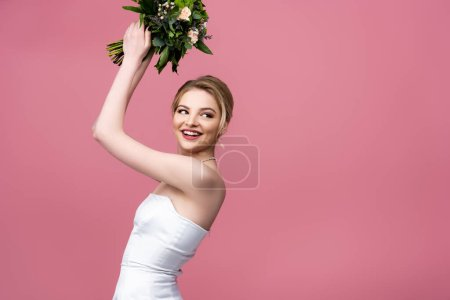 Photo for Happy bride in white wedding dress holding flowers above head isolated on pink - Royalty Free Image