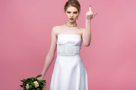 Photo pour Jolie mariée en robe de mariée blanche tenant des fleurs et montrant majeur isolé sur rose - image libre de droit