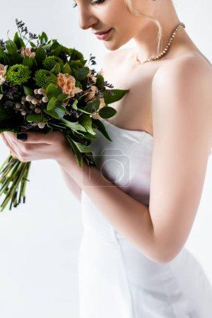 Photo pour Vue recadrée de la mariée dans une robe de mariée élégante tenant des fleurs isolées sur blanc - image libre de droit