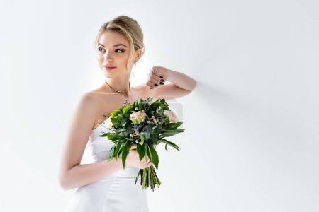 Photo pour Belle mariée dans une élégante robe de mariée tenant des fleurs sur blanc - image libre de droit