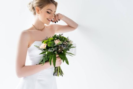 Photo for Happy young bride in elegant wedding dress holding flowers on white - Royalty Free Image
