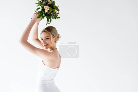 Photo for Young and cheerful bride in elegant wedding dress holding flowers above head isolated on white - Royalty Free Image