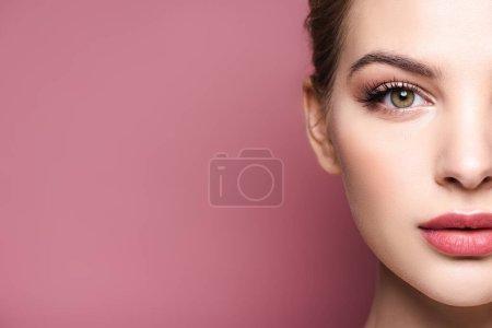 Photo pour Vue recadrée de jeune femme regardant la caméra isolée sur rose - image libre de droit