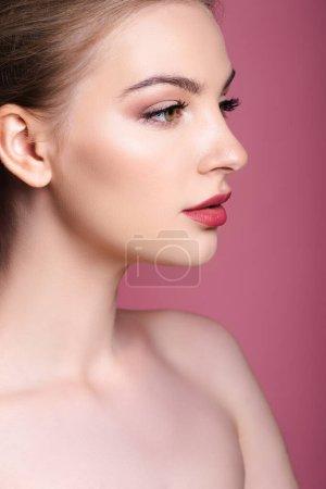 Photo pour Nu et jeune femme avec maquillage regardant loin sur rose - image libre de droit
