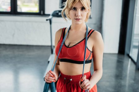 Photo for Attractive sportswoman touching skipping rope and looking at camera - Royalty Free Image