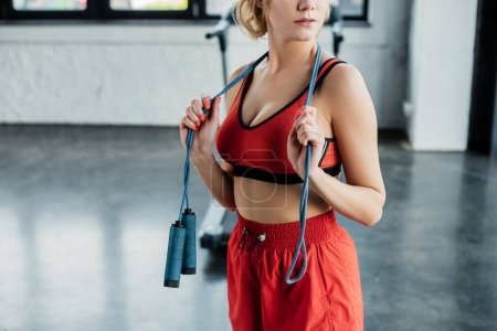 cropped view of sportswoman touching skipping rope in gym