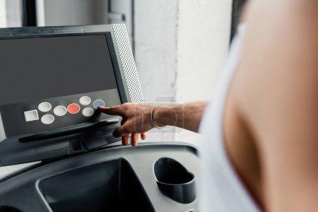 Photo pour Vue recadrée du sportif pointant avec le doigt vers le bouton sur le tapis roulant dans la salle de gym - image libre de droit